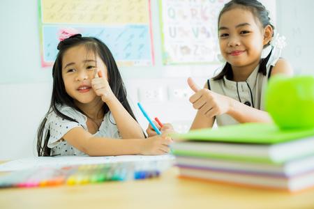 Photo pour Asian cute little child girl drawing at home - image libre de droit
