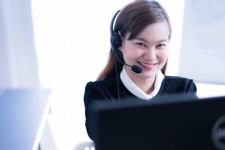 Photo pour Asian young woman working in call centre - image libre de droit