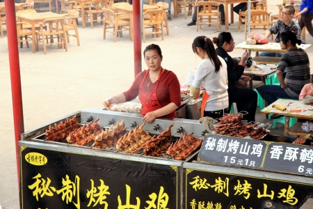 Chongqing, China, March 19, 2012 - A woman in charge of a BBQ stand at an outdoor market in Chongqing