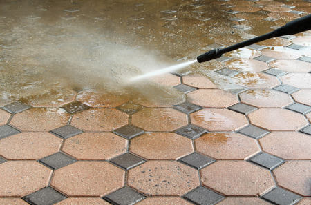 Photo pour Cleaning concrete block floor by high pressure water jet. - image libre de droit