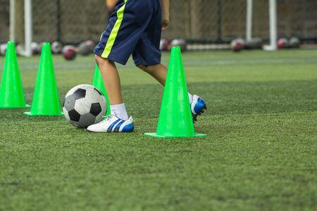 Foto de Soccer ball tactics on grass field with cone for training thailand in  background Training children in Soccer academy - Imagen libre de derechos