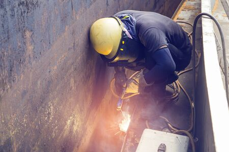 Male  worker wearing protective clothing repair  storage tank oil construction smoke inside confined spaces.