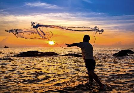 Foto de throwing fishing net during sunset , thai - Imagen libre de derechos