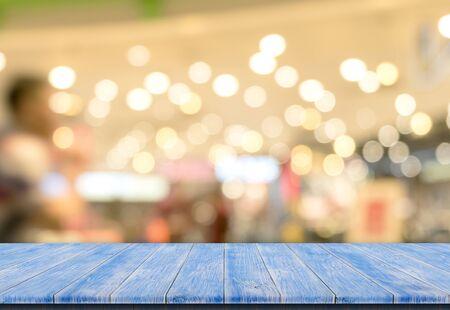 Foto de Bokeh background with empty blue wooden deck table for product montage display - Imagen libre de derechos