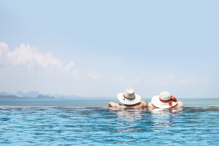 male and female models in the swimming pool wearing hats facing to the sea, beautiful summer vacation poster background, happy tour, enjoy travel, tourism, fun trip