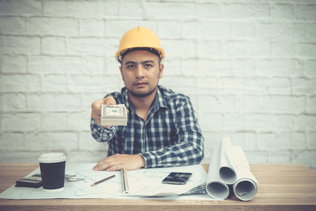 Engineer or Architect sitting, working at his desk in the office. young bearded male giving money to you. selective focus on money. vintage tone.