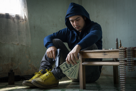 Terrorist sitting in dark and dirty room feeling despair, depressed and sad thinking about bad things. Young hopeless man hands holding gun and money. Drug dealer, criminal with weapons concept.