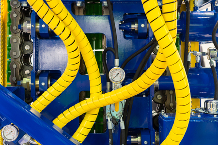 Photo for Fragment of powerful drilling equipment. Yellow hydraulic hoses, steel frame, pressure gauge - Royalty Free Image