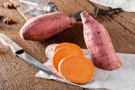 raw sweet potato over old wood background