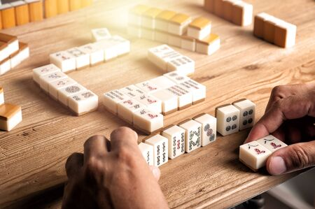 Foto de Playing Mahjong on wooden table. Mahjong is the ancient asian board game. - Imagen libre de derechos