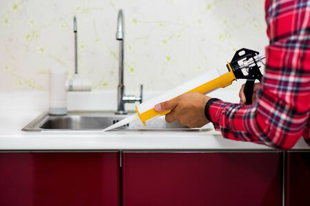 Photo for The man applying silicone sealant. The man fixing home. - Royalty Free Image