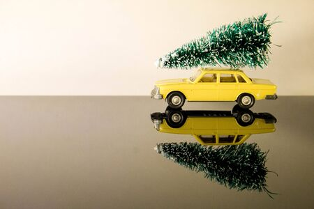 A car against a blank background sits with a lovely green Christmas tree on the roof.
