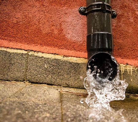 Gutters gush with water from a heavy downpour of rain.