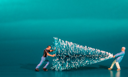 Foto de A small figure moving a Christmas Tree. - Imagen libre de derechos