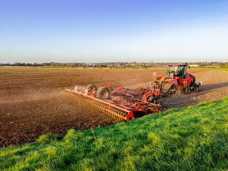 A lovely summer's evening on flat British countryside land, open fields with grass and ploughed land as the sun sets in the background.
