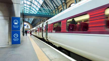 Foto de Passengers hurry along a platform in a London train station so they can board the train to get them to their next destination. - Imagen libre de derechos