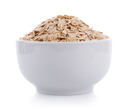Photo for Oat flakes pile in white bowl on white - Royalty Free Image