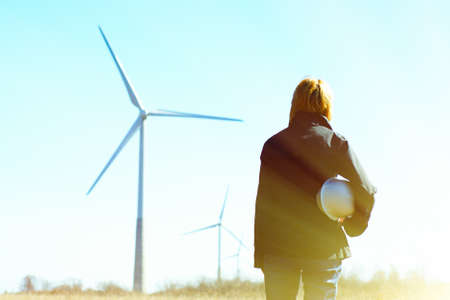 Foto de Woman engineer or architect with white safety hat and wind turbines on background - Imagen libre de derechos