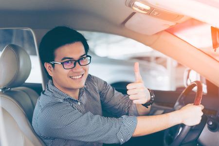 Foto de Portrait of asian happy handsome man showing thumbs up while driving car - Imagen libre de derechos