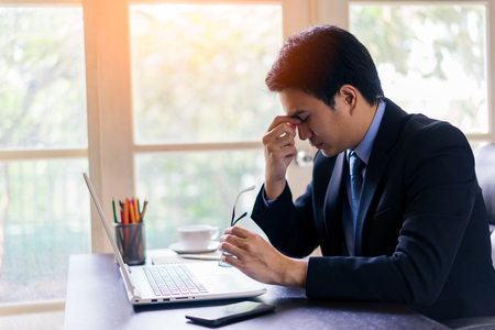 Exhausted tired young asian businessman working on laptop at office, massaging nose bridge and holding glasses.