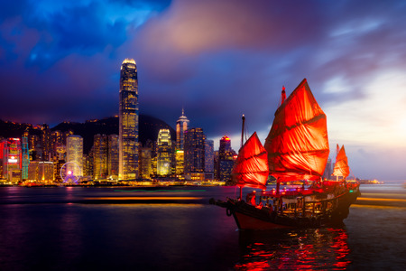 Photo for Hong Kong City skyline with tourist sailboat at night. View from across Victoria Harbor Hong Kong. - Royalty Free Image