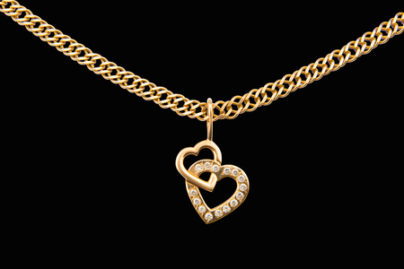 Foto de Gold chain and pendant in the shape of heart on a white background - Imagen libre de derechos