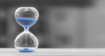 Photo pour Hourglass with blue sand on a blurred black and white background, sand trending color - image libre de droit