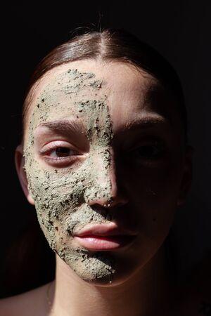 Photo pour Woman face with organic cosmetic green mask. Black background - image libre de droit