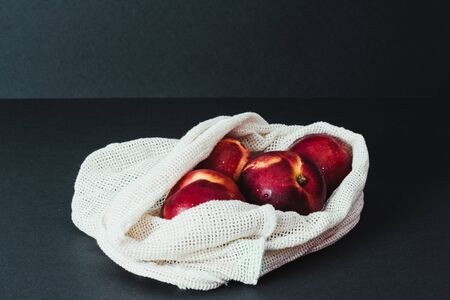 Photo for Nectarines in string bag, shopper on the black background, zero waste concept - Royalty Free Image