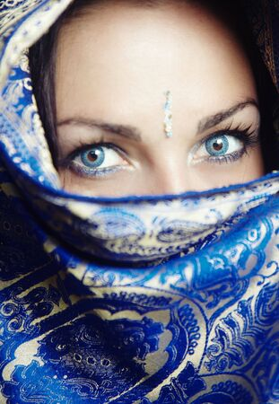 Close-up portrait of the female face in blue sari. Vertical photo