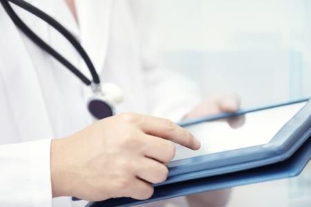 Hands of doctor indoors using tablet computer