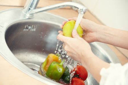 Hands of woman washing vegetables at her kitchen