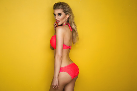 Photo for Sexy blonde woman wearing pink swimwear posing on yellow background. Perfect body - Royalty Free Image
