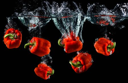 Photo pour Water droping red bell pepper or paprika with splashing water in black background. - image libre de droit