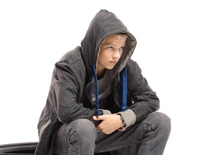 Depressed teenage boy in a jacket. Isolated on white background