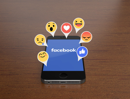 Photo pour KIEV, UKRAINE - MARCH 4, 2016: Smartphone with mobile application of Facebook on the screen and the Like Button with 6 Empathetic Emoji - image libre de droit