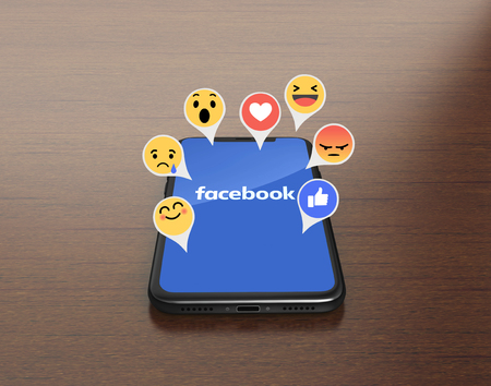 Photo for Kiev, Ukraine - January 4, 2018: 3D Render of a black iPhone X with mobile application of Facebook on the screen with Empathetic Emoji - Royalty Free Image
