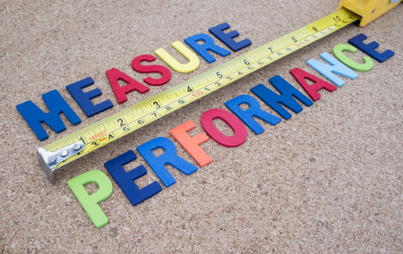 Word spelling Measure Performance and measuring tape on cork board background