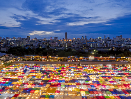 High view of colorful tent retail shop with night light at twilight time (Talad Rod Fai Night Market, Ratchada, Bangkok, Thailand)