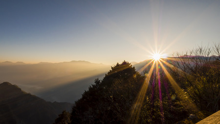 Foto de Sunrise over mountain with flare in the morning at Zhushan station, Alishan National Park, Taiwan. - Imagen libre de derechos