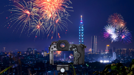 Foto de Digital camera over tripod on blur of firework with cityscape night light view of Taipei. Taiwan city skyline at twilight time - Imagen libre de derechos