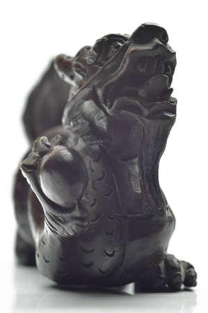 Chinese dragon made of ebony, closeup on white background