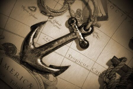 An anchor attached to rope over a vintage map
