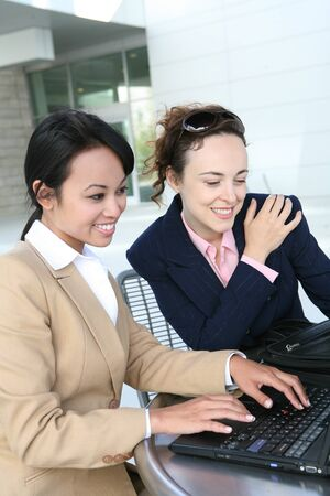 Two pretty business women working on the laptop computer