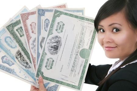 A pretty asian businesswoman holding old stock certificates