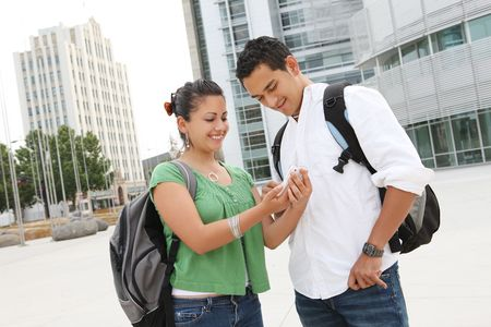Attractive students at college texting with mobile phone