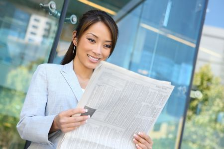 A young attractive asian business woman reading  newspaper
