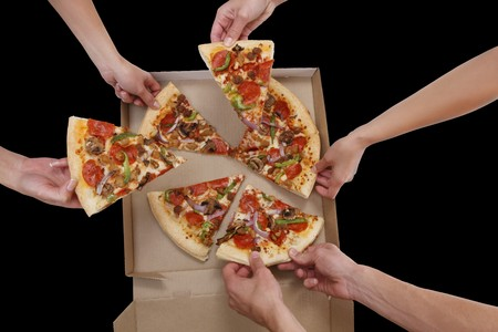 A group of people taking slices of pizza