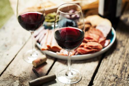 Photo pour Red wine with charcuterie assortment on the background - image libre de droit