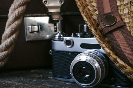 Retro summer sea vacation background. Vintage suitcase, rope, film photo camera, and hat on tourist table. Front view, close up photo.